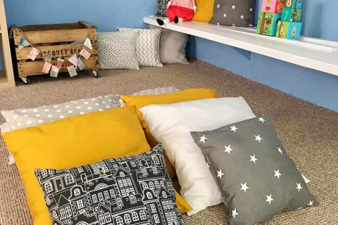 kid's space with pillows and bookshelves